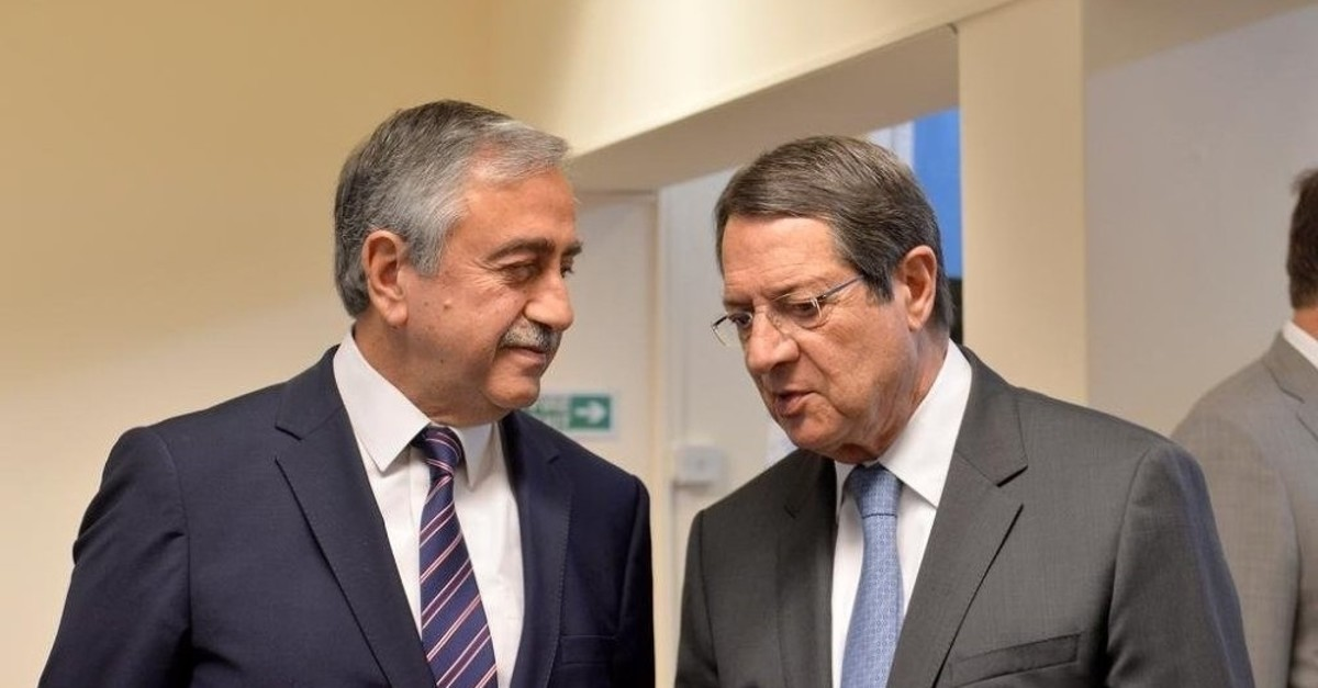 Turkish Cypriot President Mustafa Aku0131ncu0131 (left) speaks with Greek Cypriot leader Nicos Anastasiades (right) (Reuters File Photo)