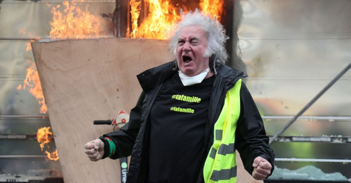A Yellow Vest protester gestures in front of a newsagent set alight during clashes with riot police forces on the Champs-Elysees in Paris on March 16, 2019. (AFP Photo)