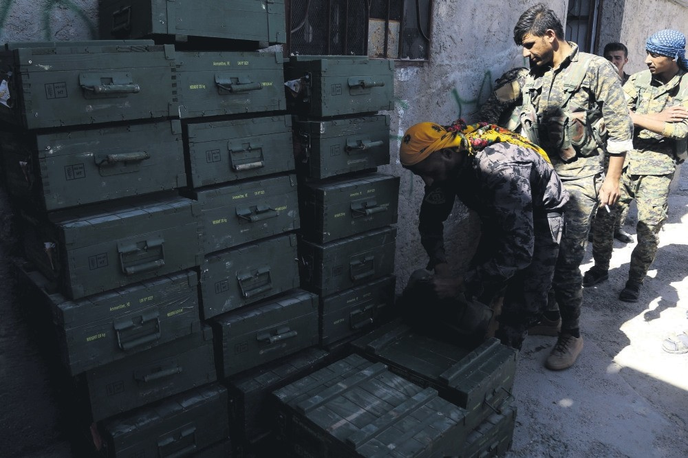 YPG-led Syrian Democratic Forces (SDF) unload boxes of ammunition supplied by the U.S.-led coalition in a village north of Raqqa, June 7, 2017.