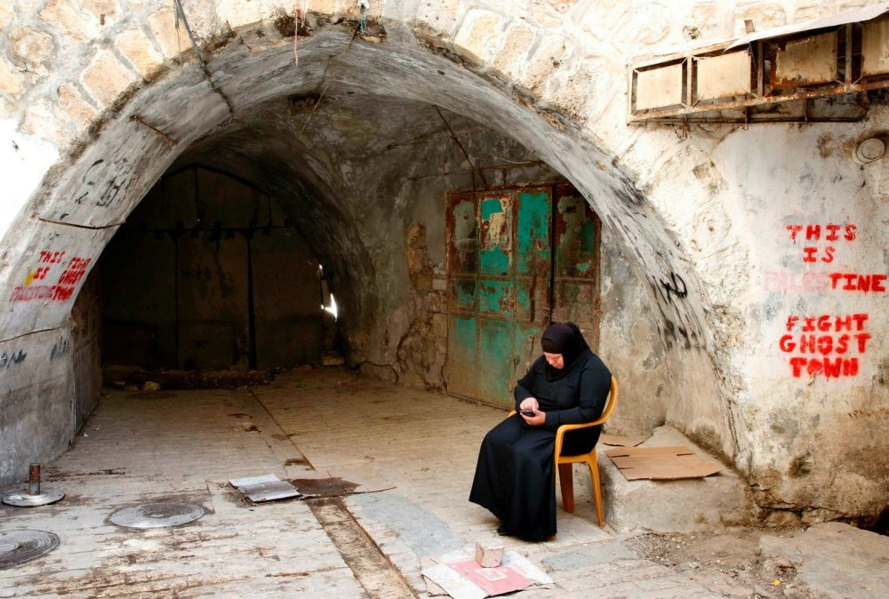 A Palestinian woman sits in the West Bank city of Hebron, May 8, 2017.