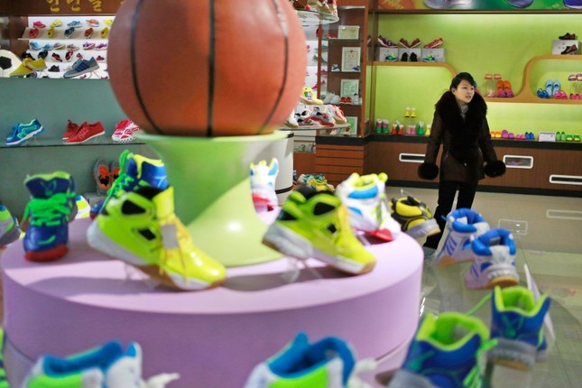 In this Friday, Feb. 1, 2019, photo, a guide stands near a basketball shoe display in a product exhibition room at the Ryuwon Shoe Factory that specializes in sports footwear, in Pyongyang, North Korea. (AP Photo)