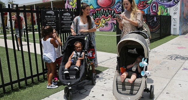 Vanessa Gomez, 33, left, with her son Ezra, 2, and her friend Cristy Fernandez, 33, with her 9-month-old- son River, of Miami, walk in the Wynwood neighborhood of Miami, Friday, July 29, 2016. (AP Photo)