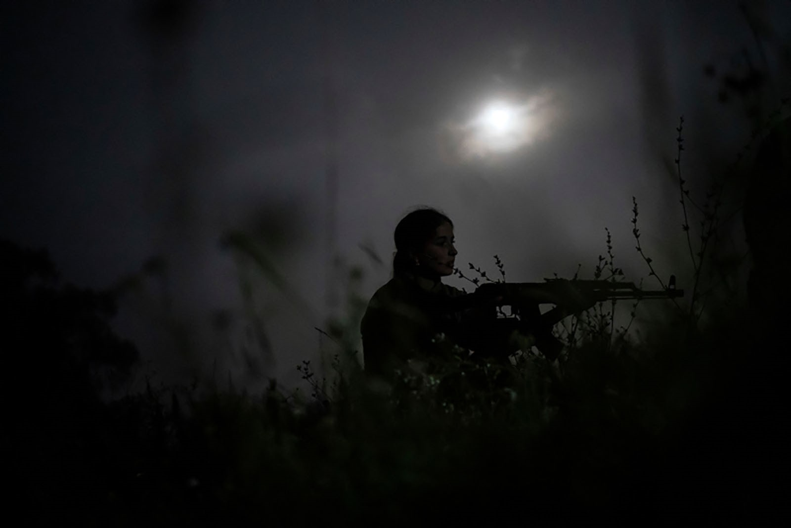 A young participant of the camp takes position with her unloaded AK-47 rifle during a night exercise.