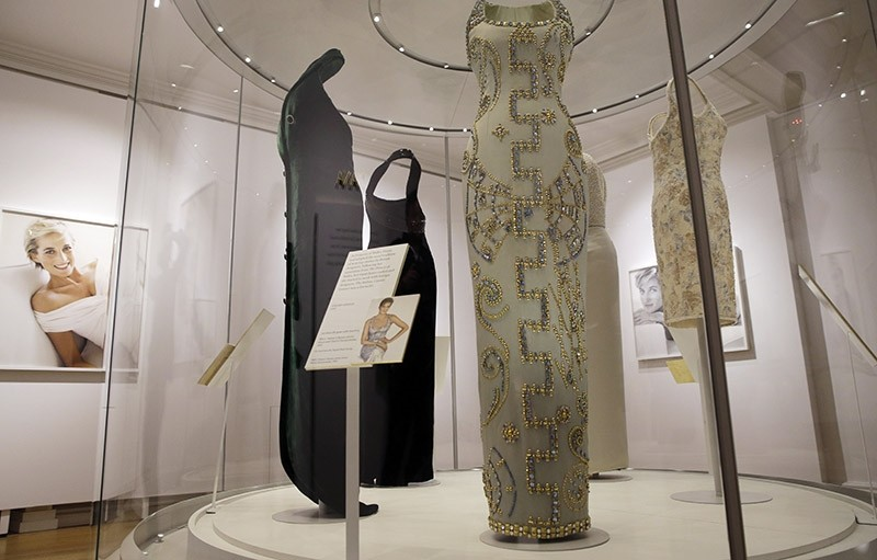 A Versace ice blue silk gown with beading, centre, worn by Diana, Princess of Wales in 1991 for a Bazaar magazine shoot,  is on display during a media preview of an exhibition of 25 dresses and outfits worn by Diana on Feb. 22, 2017. (AP Photo)