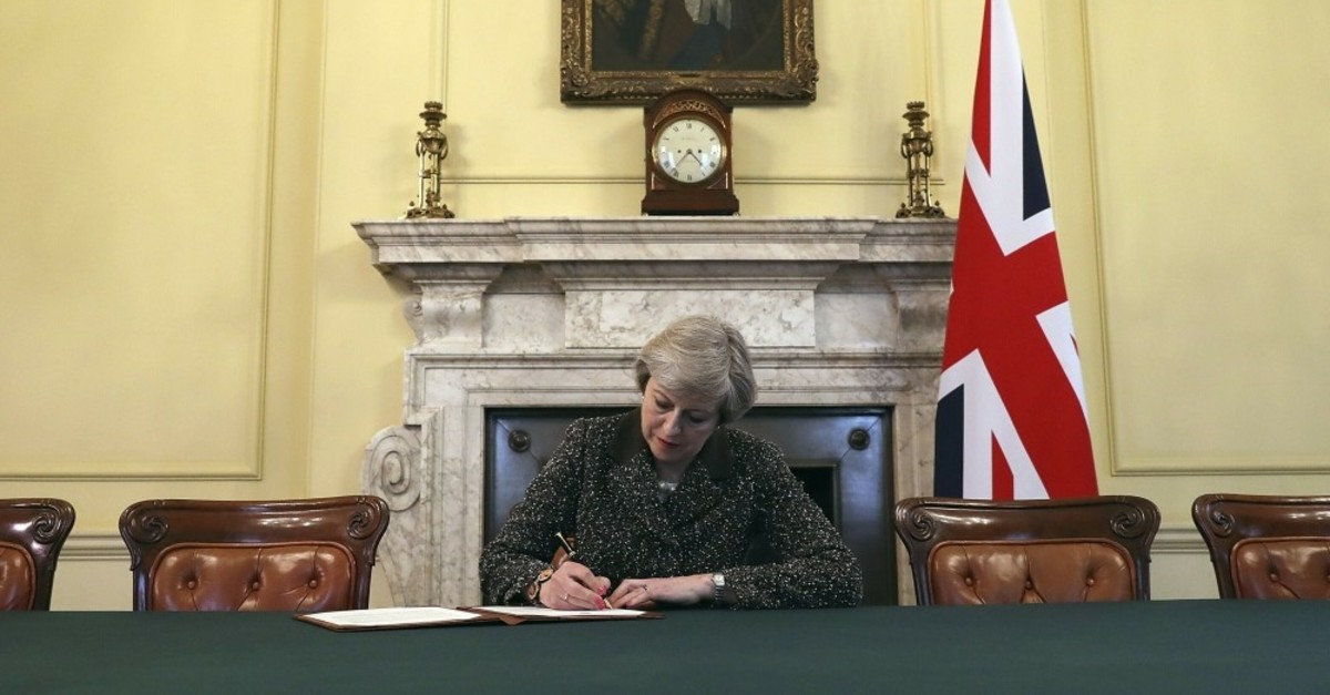 Britain's Prime Minister Theresa May, sitting below a painting of Britain's first Prime Minister Robert Walpole, signs the official letter to European Council President Donald Tusk, in 10 Downing Street, London, March 28, 2017.