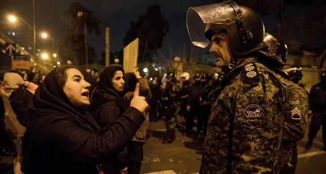 A woman talks to a policeman and asks for his sympathy at the gate of Amri Kabir University, Tehran, Jan. 11, 2020. ISNA via AP