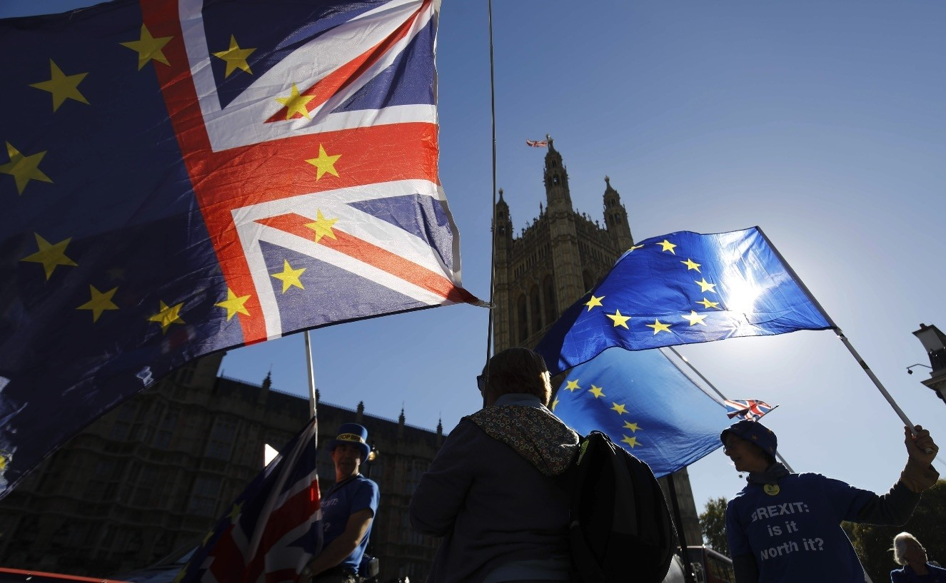 Anti-Brexit campaigner Steve Bray (L) and other activists stand outside parliament with EU and Union Flags as they protest in  Parliament Square in London, Oct. 9.