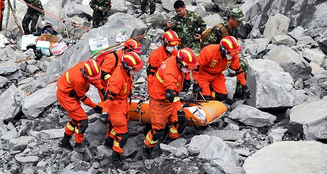 Rescue workers evacuate a body from the site of a landslide in the village of Xinmo, Mao County, Sichuan Province, China June 25, 2017. (Reuters Photo)