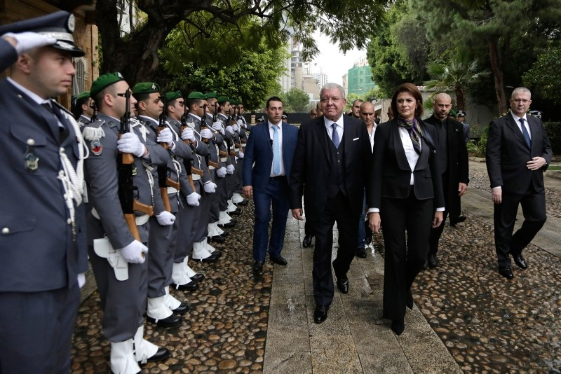 Newly appointed Interior Minister Raya El Hassan, third right, and former Lebanese Interior Minister Nohad Machnouk, center, review an honor guard during a ceremony at the interior ministry in Beirut (AP Photo)