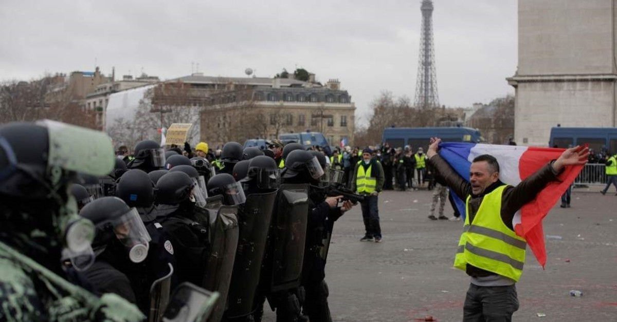 A protester holds a French flag as he faces police during the yellow vest protests, Paris, Jan. 12, 2019. (AFP Photo)