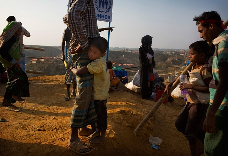 A Rohingya refugee boy who was staying in a no-man's land at Bandarban between Myanmar and Bangladesh border, clings to his father after arriving at the Balukhali refugee camp, 50 km from Cox's Bazar, Bangladesh, Jan. 24, 2018. (AP Photo)