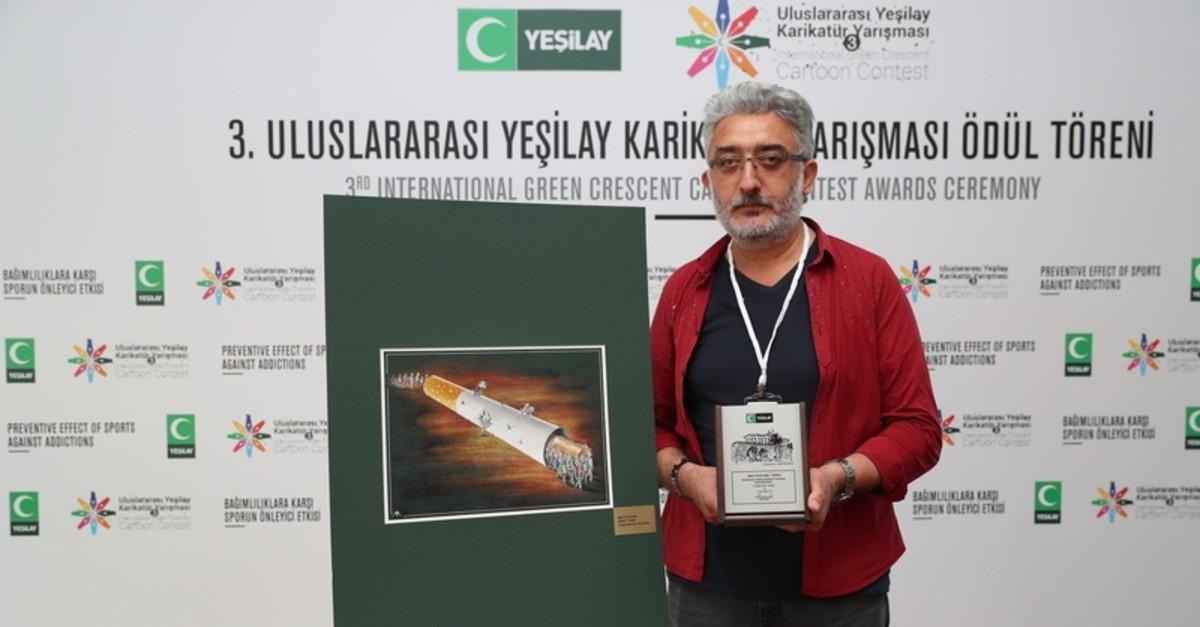 Grand prize winner Au015fku0131n Ayrancu0131ou011flu poses next to his work.