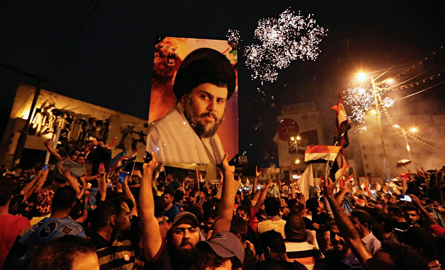 Supporters of Shiite cleric Muqtada al-Sadr, carry his image as they celebrate in Tahrir Square, Baghdad, Iraq.
