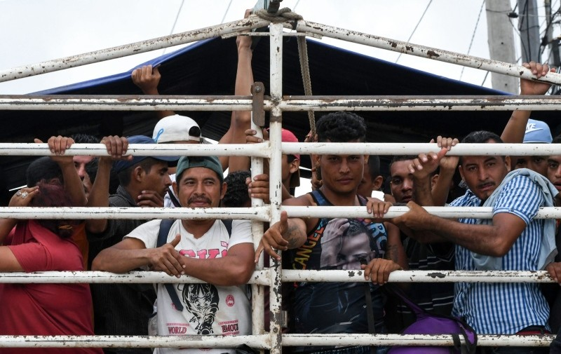 Honduran migrants aboard a truck arrive in in Guatemala City, while taking part in a caravan towards the United States, on October 17, 2018. (AFP Photo)