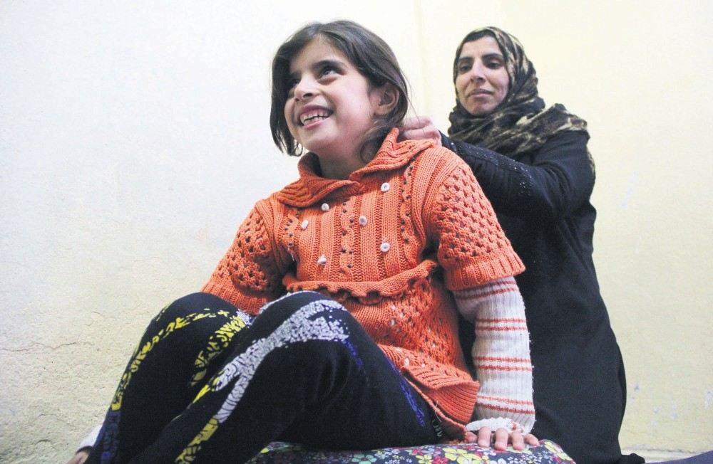 Ahlam with her mother. Her chances of survival were u2018slim' according to doctors, but the girl survived both her rare condition and bomb attacks in her war-torn homeland.