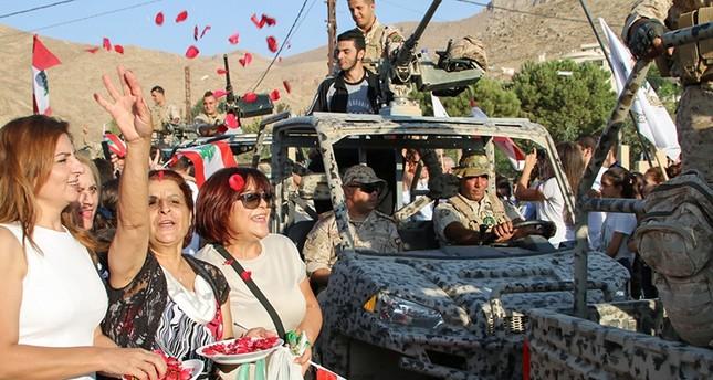 لبنانيون يحتفلون بالنصر مع عناصر من حزب الله (الفرنسية)