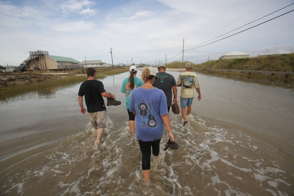 People walk through streets flooded from Hurricane Nate on Dauphin Island, Alabama.