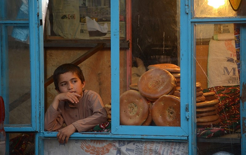 In this photograph taken on June 1, 2018, a young Afghan boy sits at a bakery as he waits to sell bread in Mazar-i-Sharif. (AFP Photo)