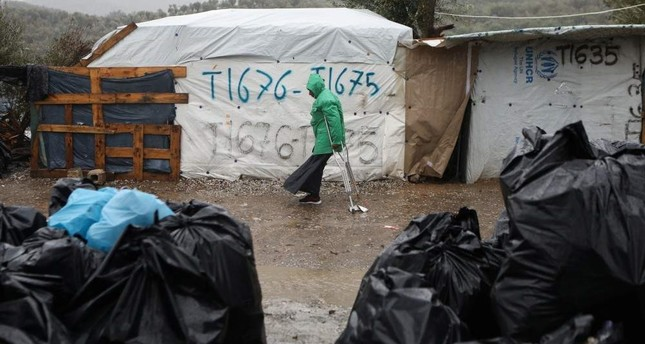 A migrant makes his way during heavy rainfall at a temporary camp for refugees and migrants next to the Moria camp on the island of Lesbos, Feb. 6, 2020. REUTERS Photo