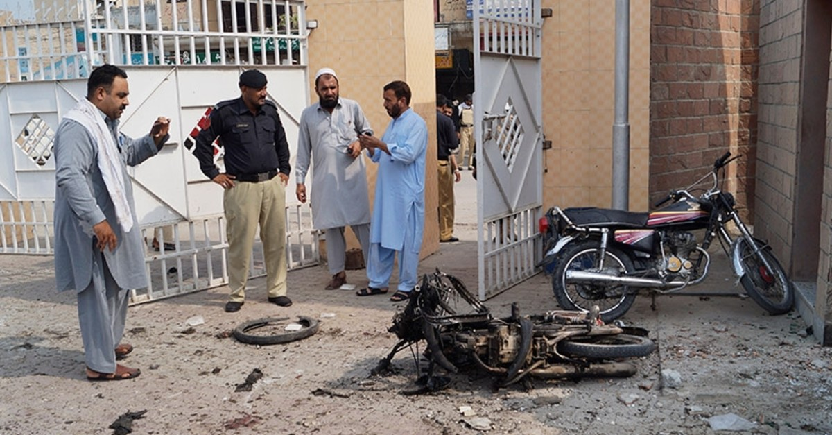 Pakistani security officials examine the site of a bombing on an entrance of a hospital in Dera Ismail Khan, Pakistan. (AP Photo)
