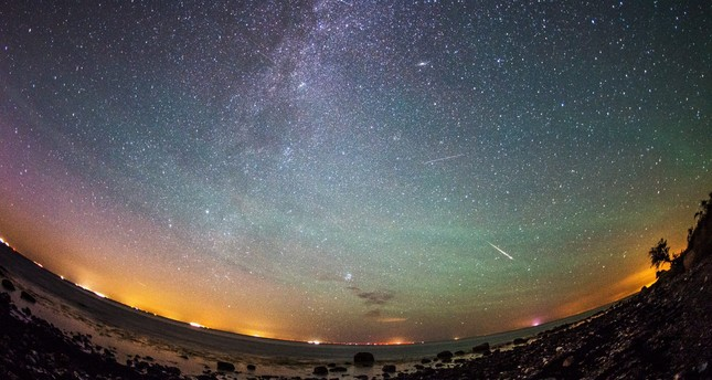 Meteors from the Perseid meteor swarm burn up in the atmosphere as our own galaxy, the Milky Way, is seen in the clear night sky over the German island of Fehmarn, Germany, early 13 August 2015. (EPA Photo)