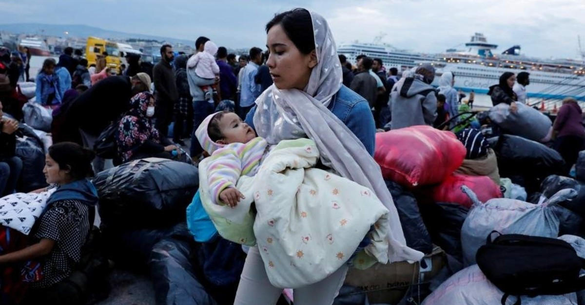 A woman holds her baby as refugees and migrants arrive on a passenger ferry from the island of Lesbos at the port of Piraeus, Oct. 7, 2019. (Reuters Photo)
