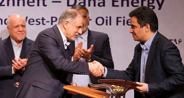 Ali Kardor Managing Director of Iran's National Oil Company (L) shakes hands with Mohammad Iravani CEO and Chairman of Dana energy after sign an oil field agreement in Tehran, on March 14, 2018. (AFP Photo)