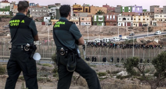 This Aug. 13, 2014, file photo shows Spanish Guardia Civil watching as would be immigrants from Africa sit atop a metallic fence that divides Morocco and the Spanish enclave of Melilla. (AFP Photo)