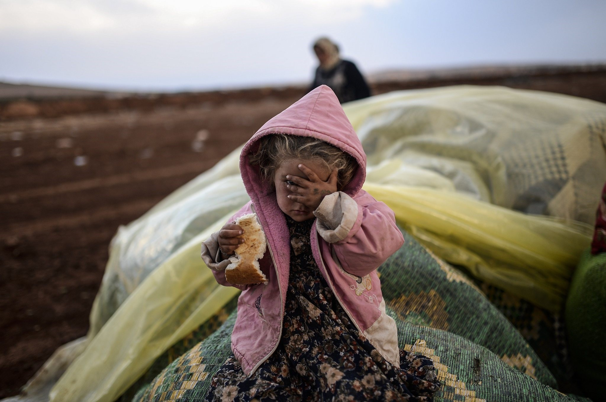 A Syrian Kurdish woman waits with her daughter near Syria border at southeastern town of Suruu00e7 in u015eanlu0131urfa. Since civil war in Syria broke out seven years ago,millions of people died and have been displaced;however, there is still no hope for peace.