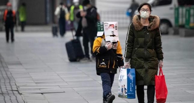 A boy wears a cardboard box on his head at the Shanghai Railway station, Shanghai, Feb. 13, 2020. AFP Photo
