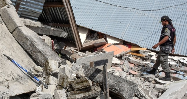 This picture taken on July 29, 2018 shows an Indonesian village security officer examining the debris of houses, after a 6.4 magnitude earthquake struck, in Lombok. (AFP Photo)