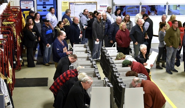 Voters wait on line to vote inside the fire bay at the Armada Twp. Fire Department, Tuesday , Nov. 6, 2018, in Armada Twp, Mich. (Todd McInturf / Detroit News via AP)