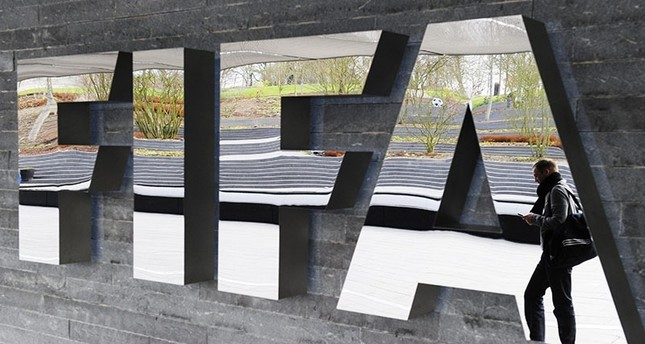 A file picture dated 19 November 2010 shows a man passing by the FIFA logo prior to a press conference following a meeting of the Executive Committee in Zurich, Switzerland. (EPA Photo)