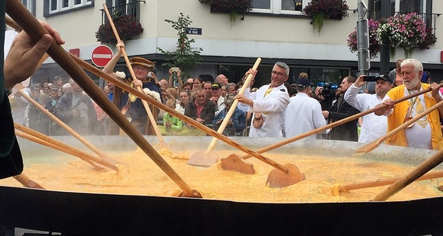 Cooks and volunteers stir eggs on an oversize pan at the 22nd Giant Omelet event in Malmedy, Belgium, Tuesday, Aug. 15, 2017 AP Photo