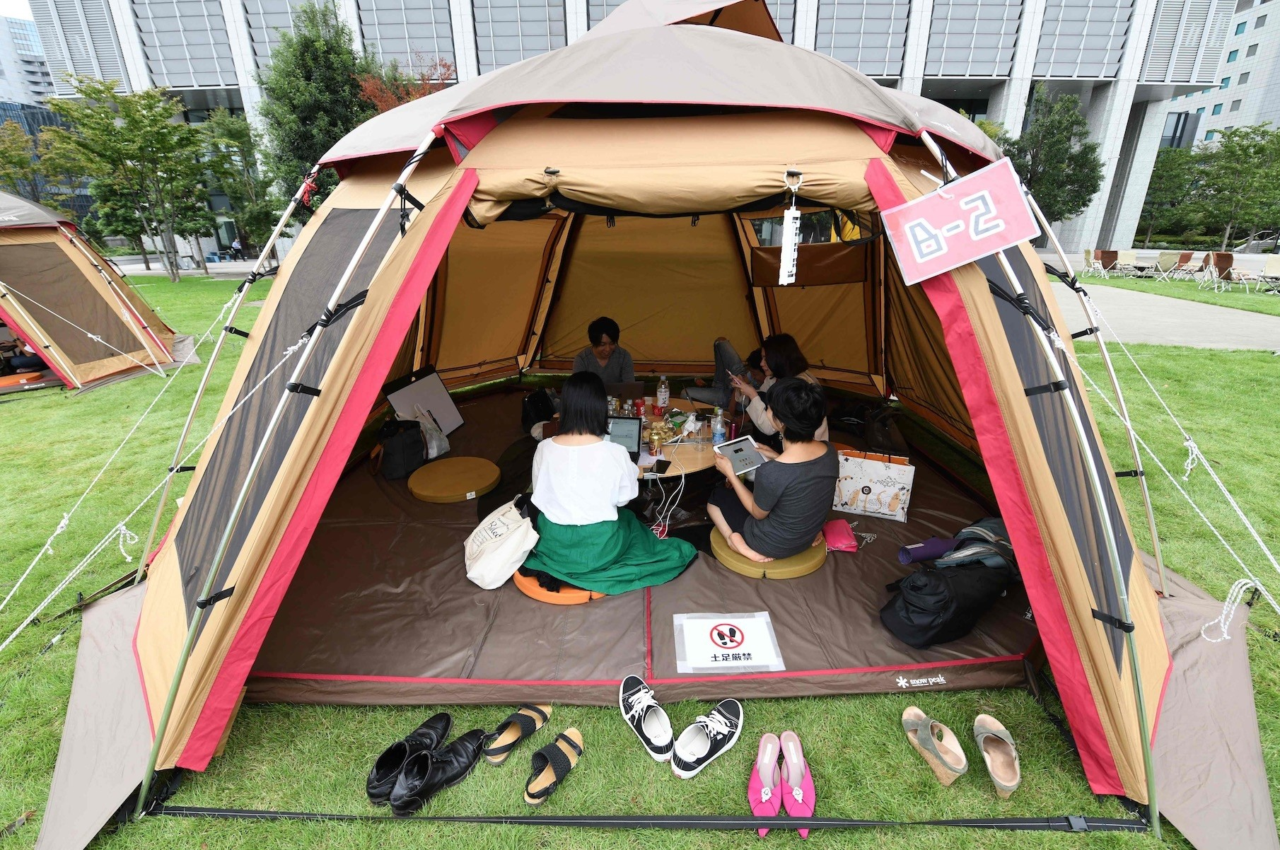 Company employees work inside camping tents erected on the lawn outside an office building in Tokyo.