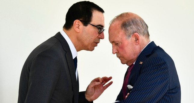 Treasury Secretary Steven Mnuchin, left, and White House chief economic adviser Larry Kudlow, right, talk along the colonnade following an immigration speech by President Donald Trump in the Rose Garden at the White House, May 16, 2019. AP Photo
