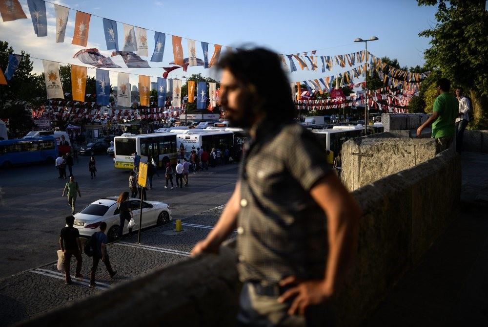 A man stands near an AK Party flag during the campaign period for elections in Istanbul, June 4, 2015.