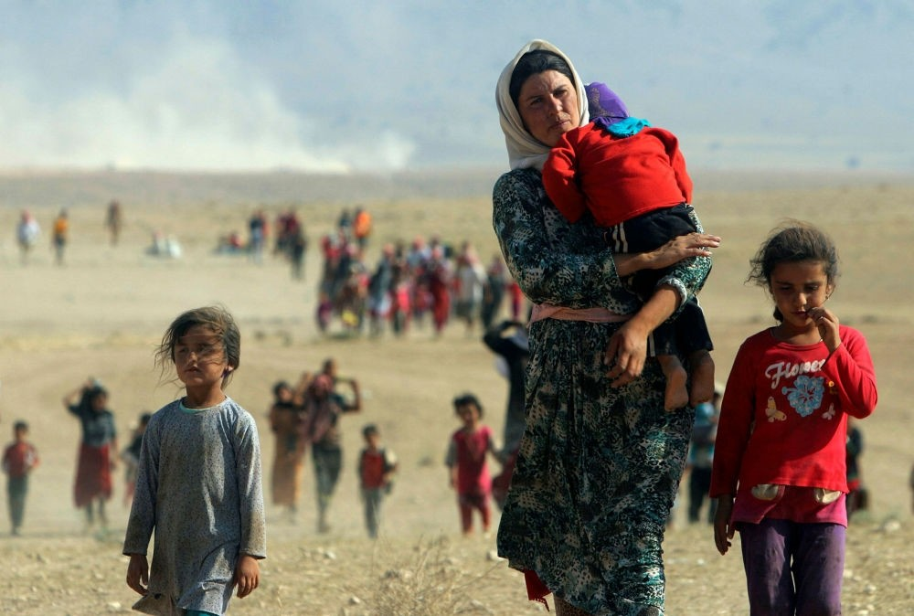 Displaced people from the minority Yazidi sect flee violence from forces loyal to Daesh in Sinjar, walk towards the Syrian border on the outskirts of the Sinjar Mountains.