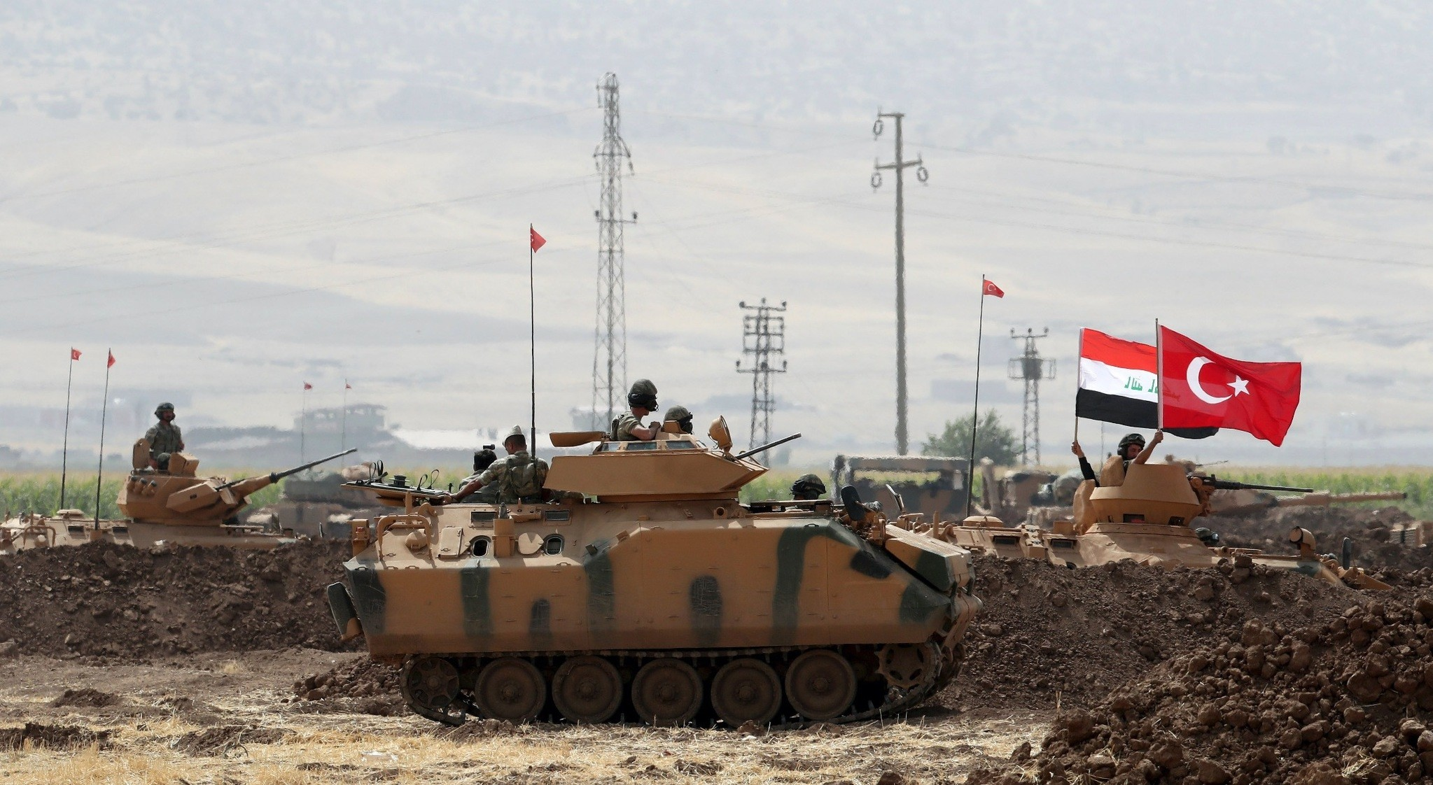 Soldiers hold the Turkish and Iraqi flags while standing in the turret of a Turkish armored vehicle participating in a military exercise near the Turkish-Iraqi border in u015eu0131rnak, Sept. 26, 2017.
