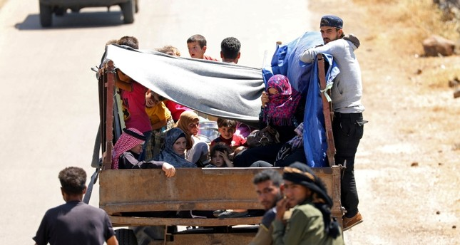 Internally displaced people from Deraa province ride on a back of a truck near the Israeli-occupied Golan Heights in Quneitra, Syria June 30, 2018. Reuters Photo