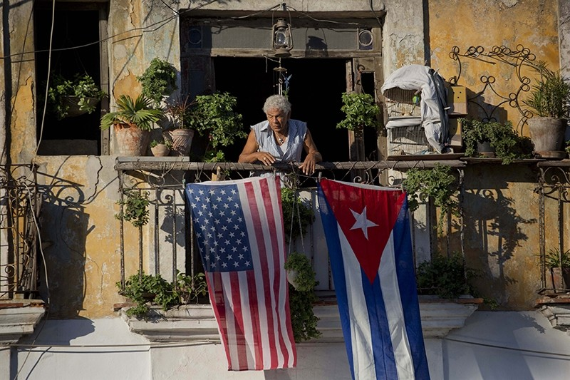 In this Dec. 19, 2014 file photo, Javier Yanez stands on his balcony decorated with U.S. and Cuban flags in Old Havana, Cuba. (AP Photo)