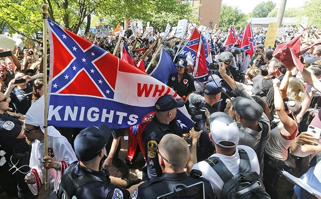 This July 8, 2017 photo shows members of the KKK escorted by police past a large group of protesters during a KKK rally in Charlottesville, Va. (AP Photo)