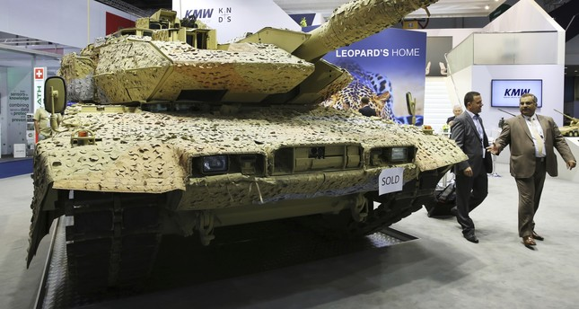Men walk past a Krauss-Maffei Wegmann Leopard tank with a sold sign on it at the International Defense Exhibition and Conference, known by the acronym IDEX, in Abu Dhabi, United Arab Emirates.  (AP Photo)