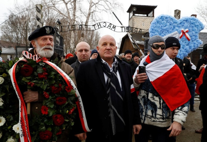 Far right activists walk past the ,Arbeit Macht Frei, gate at the former Nazi German concentration and extermination camp Auschwitz, Poland, January 27, 2019.