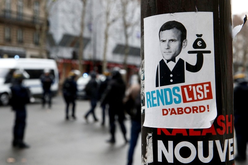 A sticker showing a portrait of French President Emmanuel Macron and the message ,Reinstall the wealth tax, is seen in a street during a national day of protest by the ,yellow vests, movement in Paris, France, December 8, 2018. (Reuters Photo)
