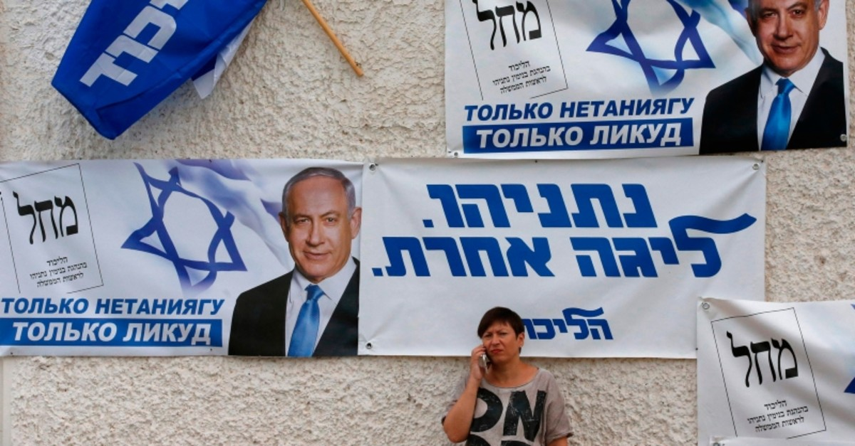 A woman talks on her mobile phone below banners for the Likud party showin chairman and Israeli Prime Minister Benjamin Netanyahu in the southern israeli city of Beersheva on Sept. 15, 2019. (AFP Photo)