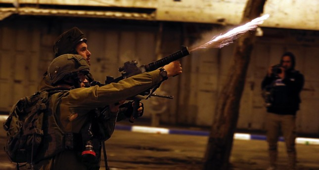 Israeli army soldiers shoot tear gas grenades during clashes with Palestinian civilian protesters, West Bank, May 14.