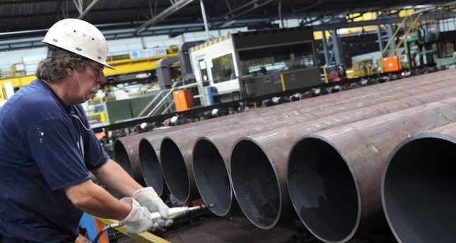 An employee checks a steel pipe in the manufacturing hall at Vallourec and Mannesmann in Duesseldorf, Germany, July 9, 2013.