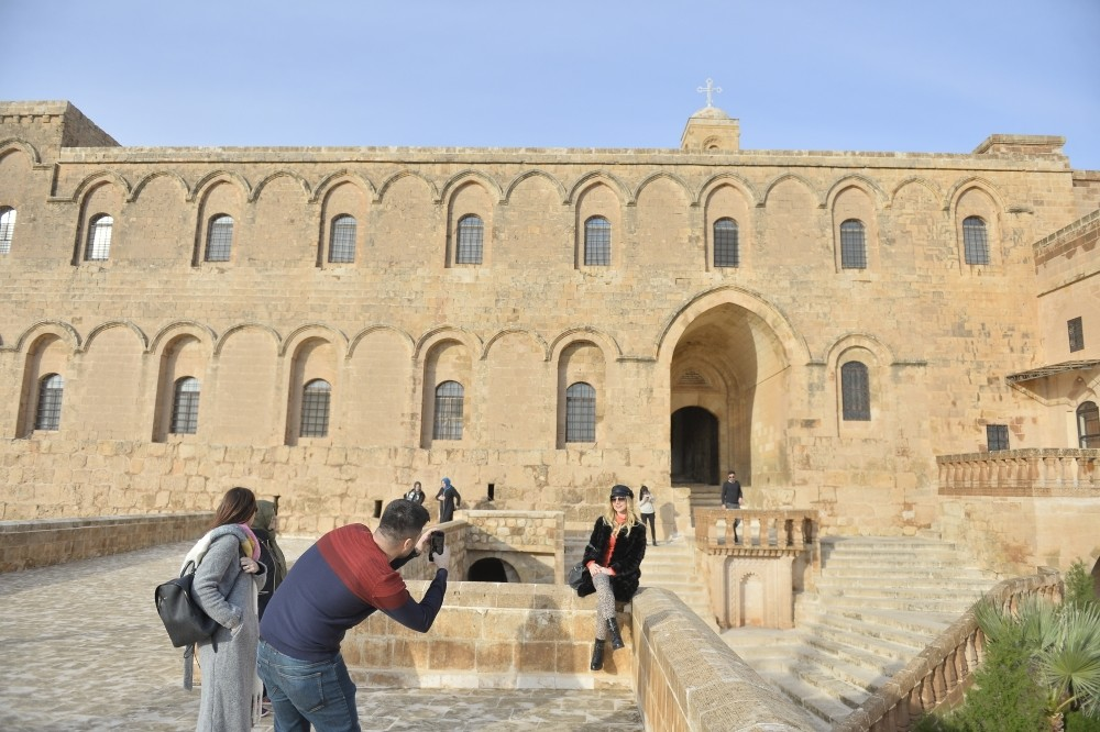 Tourists take photos in front of the Deyrulzafaran Monastery of Mardin. This Syriac Orthodox venue, known as ,saffron monastery, for the color of its stone is among the city's top touristic attractions.