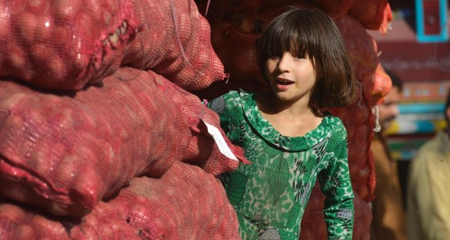A child works in a market in Lahore Today marks World Day Against Child Labour.